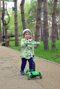 Junge 3 Jahre auf Kinderoller in grün