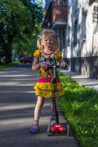 Mädchen auf Kinderoller mit 3 Rädern